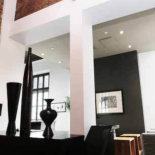 three-black-vases-on-top-of-black-wooden-furniture-beside-white-column